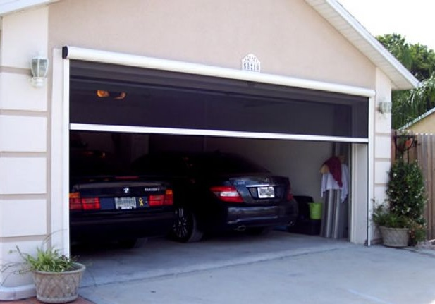 Motorized retractable garage door screen