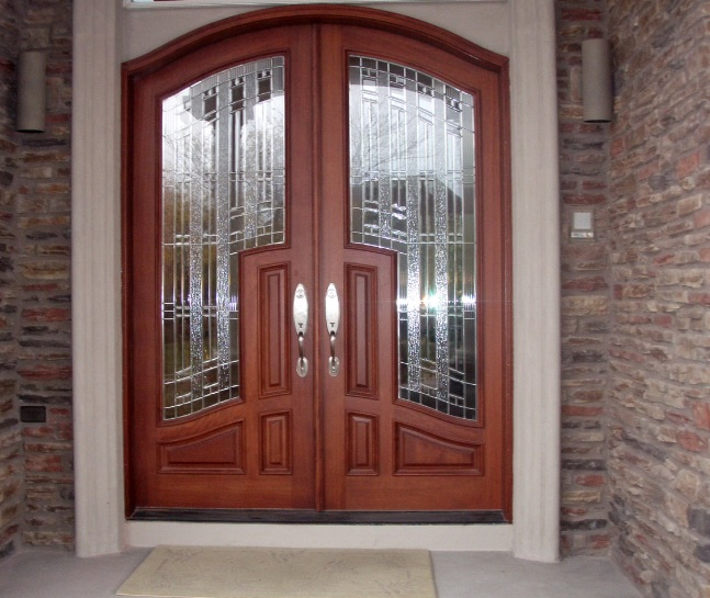 Arched mahogany entry doors with decorative glass inserts