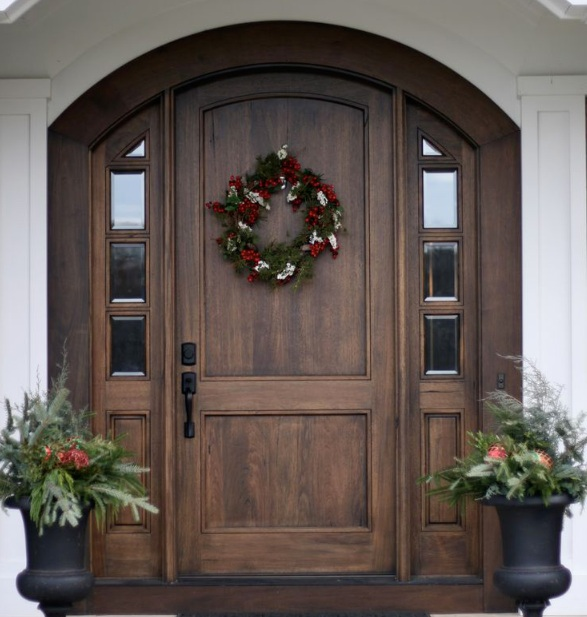Dark wood arched entry doors with classic black door handles