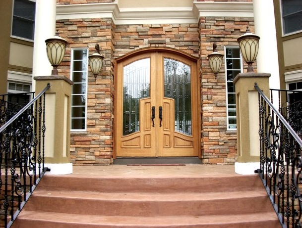 Double arched entry doors with decorative glass inserts