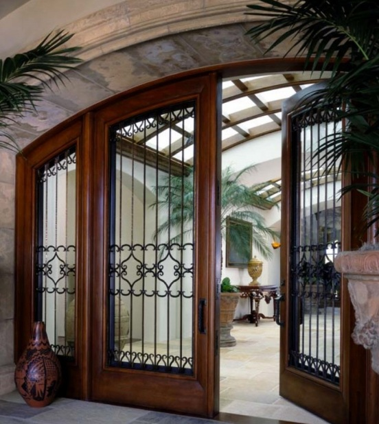 Double arched entry doors with wrought iron trellis